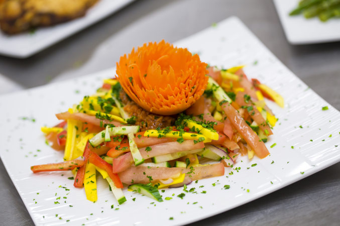 Decoratively composed plate of fruit and vegetable julienne salad sprinkled with cilantro, featuring a carrot floral decoration on top. LUC banquet hall / wedding hall catering sample food photo.