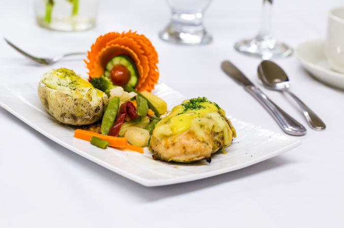 Banquet hall catering food, silverware and glasses. A garnished baked potato, sautéed or steamed veggies, stuffed chicken breast or dumpling covered in two kinds of melted cheese and sprinkled with parsley or cilantro. Decorative flower made of carrot, cucumber and grape tomato.