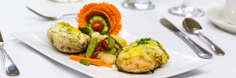 LUC banquet hall / wedding hall catering food, silverware and glasses. Garnished baked potato, sauteed vegetables, stuffed chicken breast covered with two kind of melted cheese and sprinkled with parsley or cilantro.
