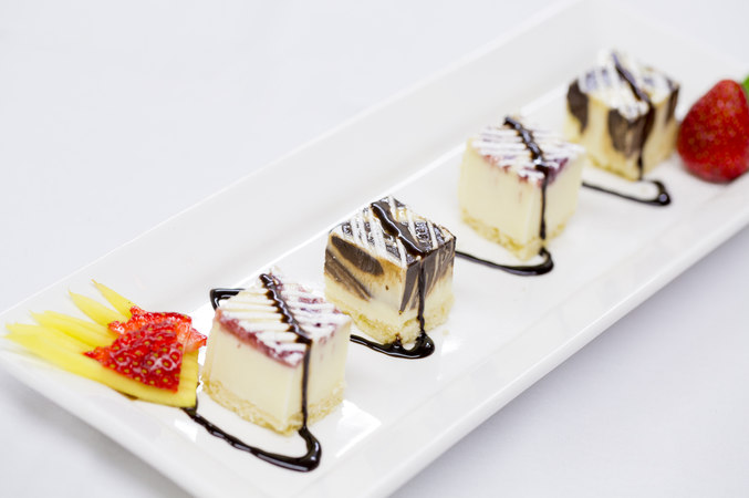 Banquet hall catering sweets. A fruit garnished desert plate with four small delectable squares of various cheesecakes, all covered with a fine decorative zigzag line of chocolate sirup or liquor.